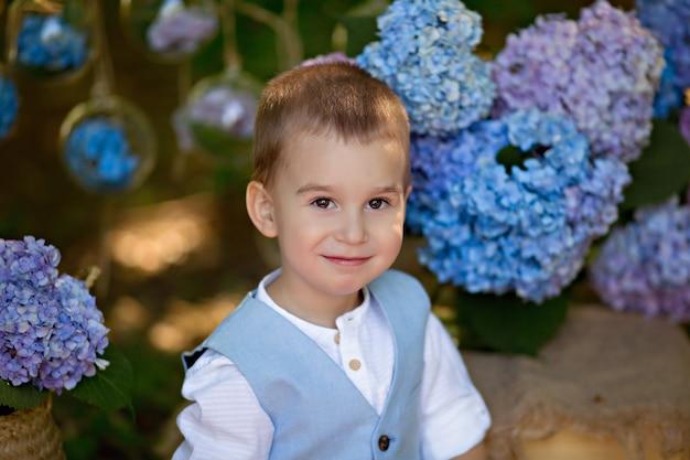 Um menino senta-se na grama na natureza com buquês de flores de hortênsia.