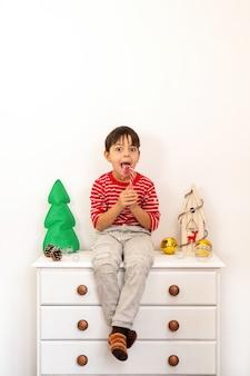Um menino sentado em uma cômoda lambendo um pirulito, um conjunto de decorações brancas com brinquedos, árvore de natal e uma casa de madeira