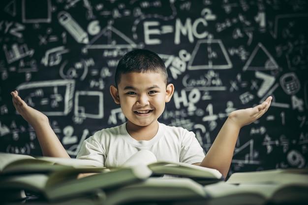 Um menino sentado na sala de aula lendo um livro