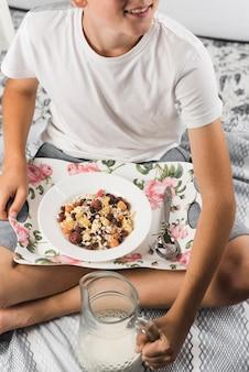 Um, menino sentando, com, bandeja, de, aveia, flocos, segurando, leite, jarro vidro