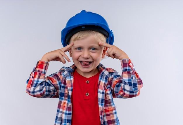 Um menino sorridente e fofo com cabelo loiro, usando uma camisa xadrez e um capacete azul apontando para a cabeça com os dedos indicadores enquanto olha para uma parede branca