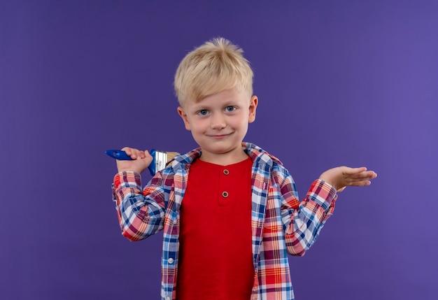 Um menino sorridente e fofo com cabelo loiro, vestindo uma camisa xadrez, segurando um pincel e olhando para uma parede roxa