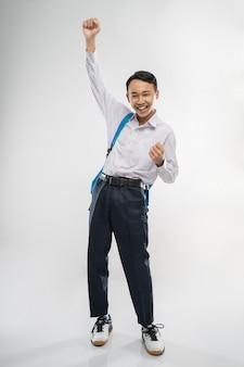 Um menino sorridente usa uniforme escolar, carrega uma mochila e levanta a mão