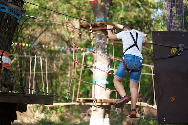 Um menino supera um obstáculo em um parque de diversões