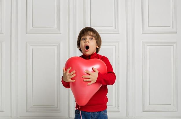 Um menino surpreso de jeans e um suéter segura um balão de coração vermelho em um fundo branco com espaço para texto