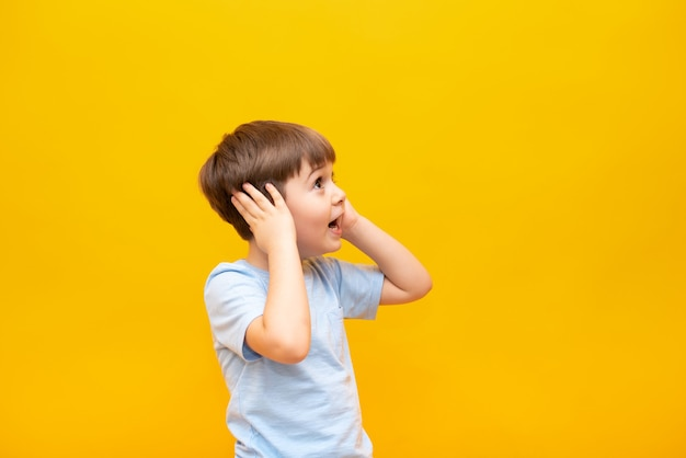 Um menino surpreso olha para o lado e segura a cabeça com as mãos. isolado em uma parede amarela