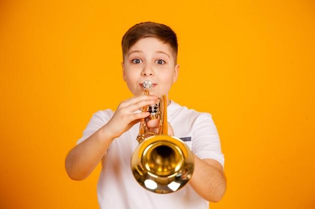 Um menino toca trompete. um adolescente bonito com uma camiseta branca toca um instrumento musical de trompete