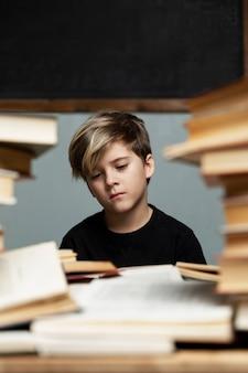 Um menino triste em uma camiseta preta está sentado a uma mesa com um monte de livros