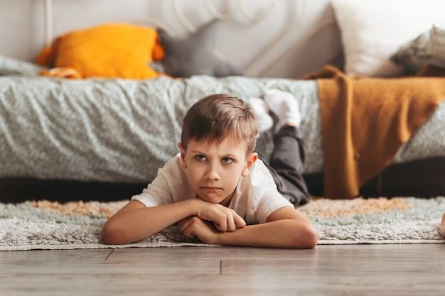 Um menino triste está deitado no chão do quarto das crianças. emoções infantis. adolescente zangado