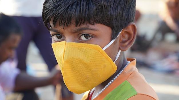 Um menino usando a máscara porque sua coroa segura