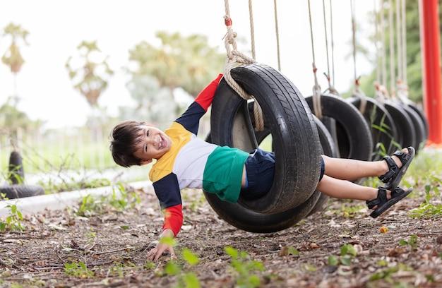Um menino vestindo roupas coloridas brilhantes, jogando o balanço do pneu pendurado no playground e se divertindo com a atividade de férias de verão saudável. Foto Premium