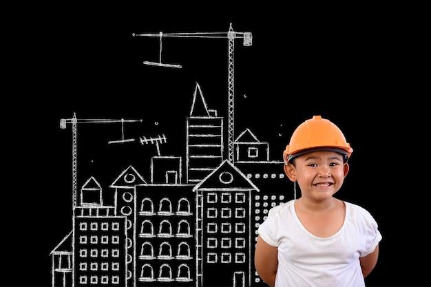 Um menino vestindo um chapéu de engenheiro e uma planta da casa em um quadro negro