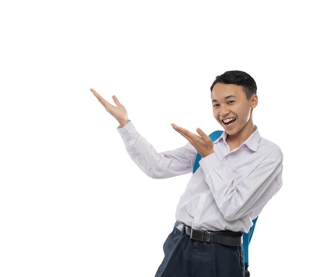 Um menino vestindo um uniforme do ensino fundamental sorri feliz ao oferecer algo com um gesto de mãos