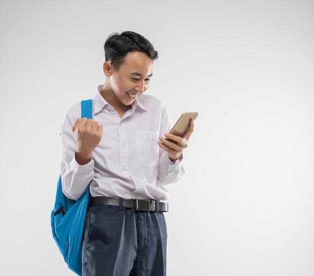 Um menino vestindo um uniforme do ensino fundamental sorri feliz ao olhar para o celular