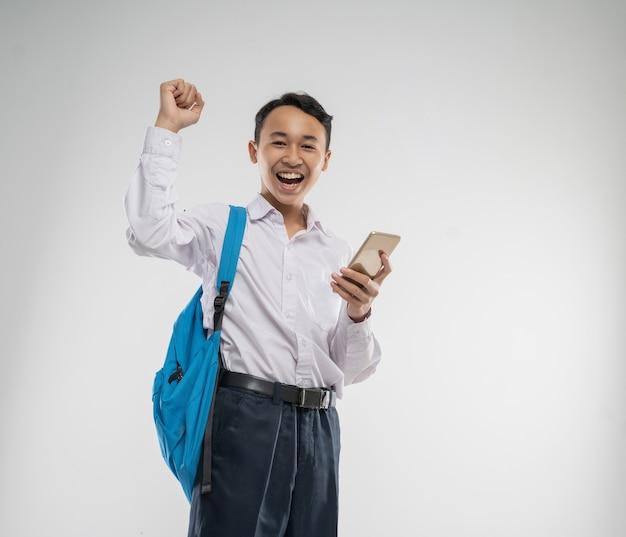 Um menino vestindo um uniforme do ensino fundamental sorriu feliz enquanto segurava um celular com a mão levantada