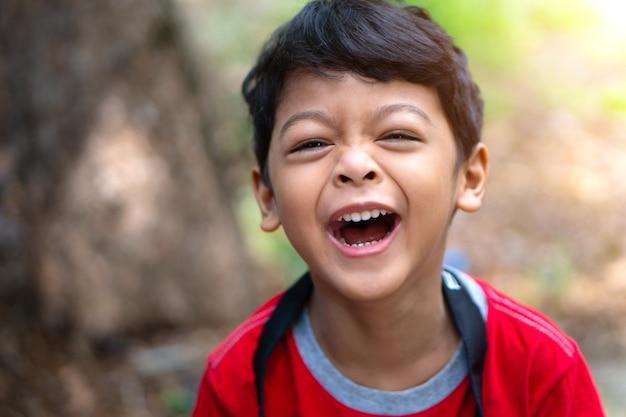 Um menino vestindo uma camisa vermelha riu feliz