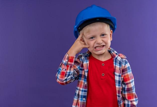 Um menino zangado e fofo com cabelo loiro, vestindo uma camisa xadrez e um capacete azul olhando