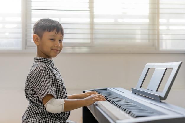 Um, meninos asian, em, a, ferido, mãos, piano jogando