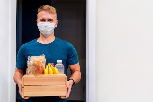 Um mensageiro com máscara entrega uma caixa de alimentos. prestação de serviço em termos de quarentena
