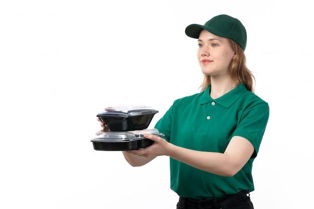 Um mensageiro feminino jovem vista frontal em uniforme verde, entregando tigelas de comida e sorrindo em branco