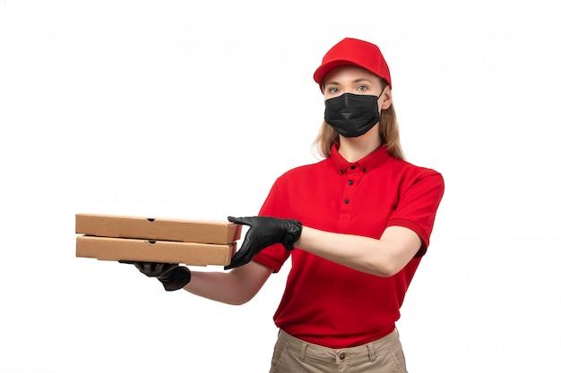 Um mensageiro feminino vista frontal de camisa vermelha, boné vermelho, luvas pretas e calças pretas de máscara marrom, segurando caixas de pizza