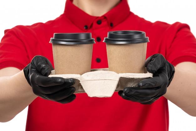 Um mensageiro feminino vista frontal em luvas de camisa vermelha preta segurando copos de café