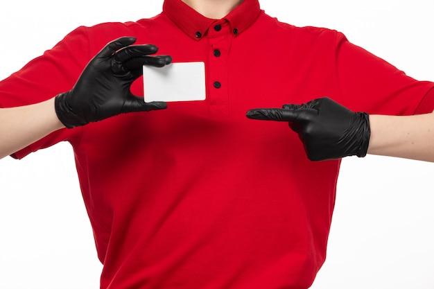 Um mensageiro feminino vista frontal em luvas de camisa vermelha preta segurando o cartão branco