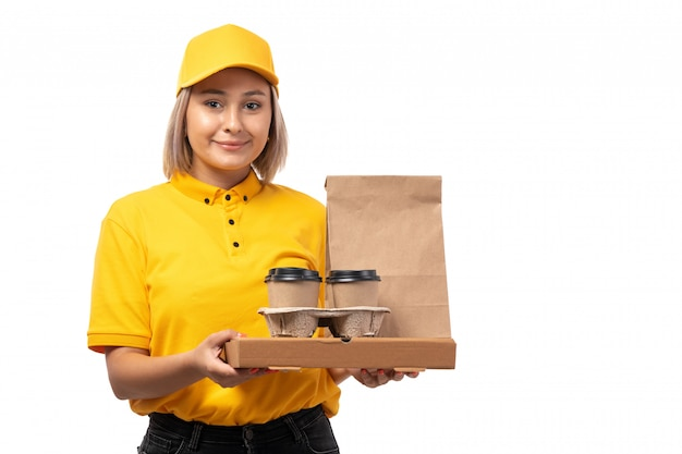 Um mensageiro feminino vista frontal na camisa amarela, boné amarelo e calça jeans preta segurando café e pacotes com comida sorrindo no serviço de fundo branco, entregando