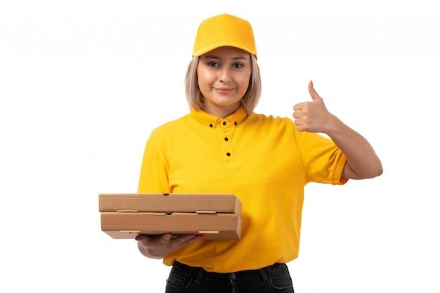 Um mensageiro feminino vista frontal na camisa amarela camisa amarela e calça jeans preta segurando caixas de pizza sorrindo mostrando como sinal em branco