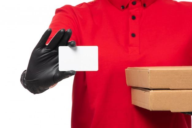 Um mensageiro feminino vista frontal na camisa vermelha boné vermelho luvas pretas e máscara preta segurando caixas de pizza e cartão branco no branco