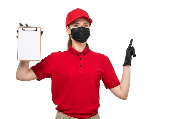 Um mensageiro feminino vista frontal na camisa vermelha boné vermelho luvas pretas e máscara preta segurando o bloco de notas em branco
