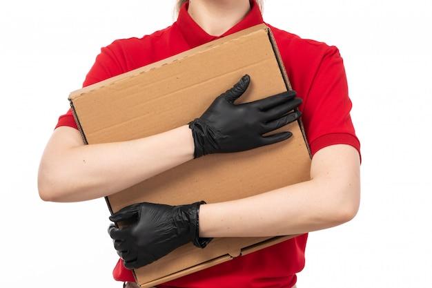 Um mensageiro feminino vista frontal na camisa vermelha boné vermelho luvas pretas e máscara preta segurando o pacote em branco