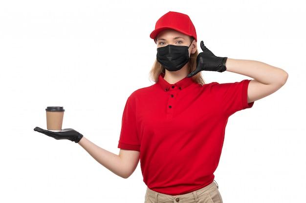 Um mensageiro feminino vista frontal na camisa vermelha luvas pretas boné vermelho máscara preta segurando café branco