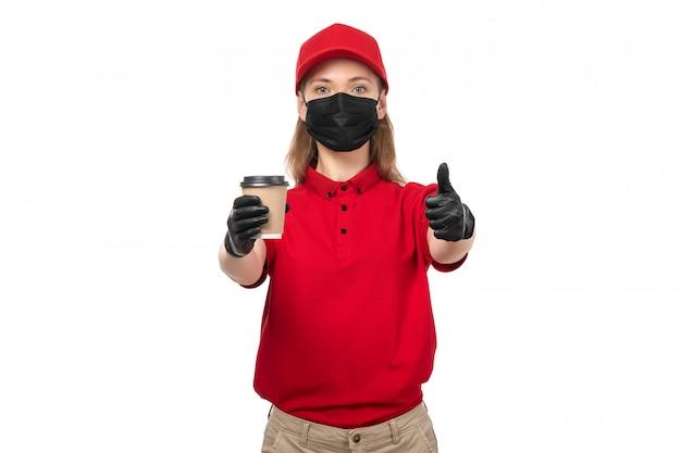 Um mensageiro feminino vista frontal na camisa vermelha máscara de luvas pretas e boné vermelho segurando a xícara de café mostrando como sinal