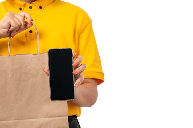 Um mensageiro feminino vista frontal na tampa amarela camisa amarela e calça jeans preta, segurando o pacote com comida e smartphone em branco