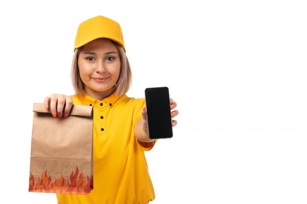 Um mensageiro feminino vista frontal na tampa amarela camisa amarela segurando o smartphone e o pacote com comida sorrindo em branco