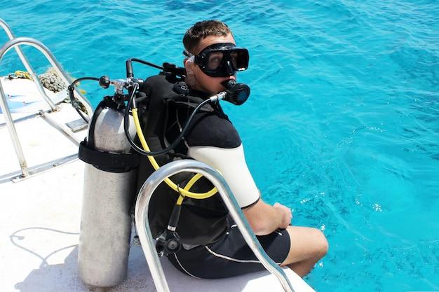 Um mergulhador em equipamento de mergulho está se preparando para mergulhar.