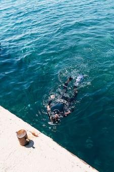 Um mergulhador em uma roupa de mergulho com nadadeiras e uma máscara com um snorkel flutua na superfície