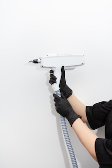 Um mestre de depilação a laser segura um aparelho de depilação a laser nas mãos. remoção de pêlos em todas as partes do corpo. máquina de remoção de cabelo.