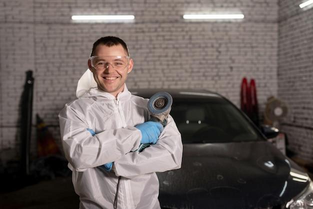 Um mestre em uma roupa de proteção está em uma estação de serviço de um carro consertado e sorri