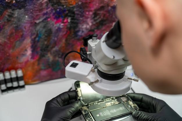Um mestre examina um smartphone com defeito através de um microscópio