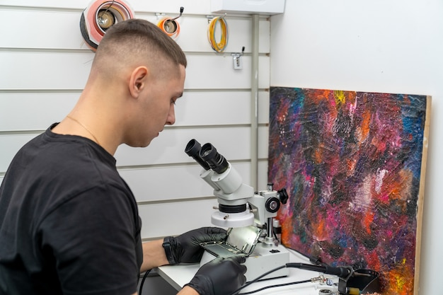 Um mestre que conserta um telefone celular por meio de um microscópio examina a microplaca instalada dentro do smartphone