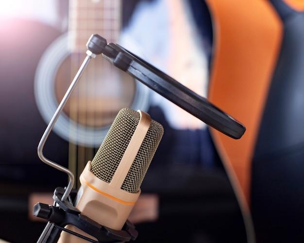Um microfone e um violão em uma mesa, estudo, teletrabalho, artistas