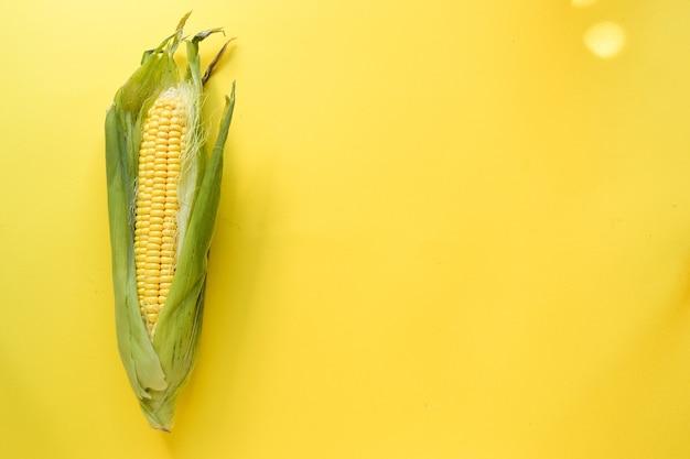 Um milho em um fundo amarelo vista superior do conceito de comida mínima
