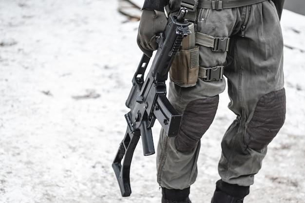 Um militar com uma metralhadora abatida está caminhando pela estrada.