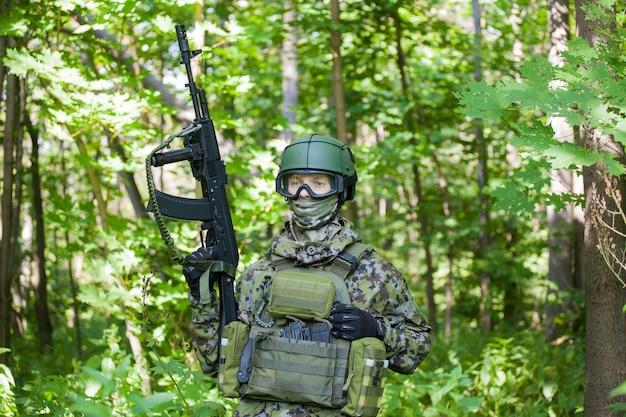 Um militar na floresta com uma metralhadora em tempo de paz. preparando os militares para as hostilidades.