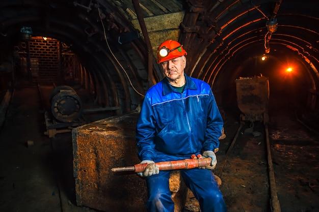 Um mineiro em uma mina de carvão está perto de um carrinho. copie o espaço.