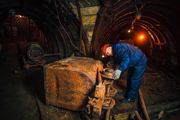 Um mineiro em uma mina de carvão fica perto de um carrinho. copie o espaço. mineiro, reparando um carrinho