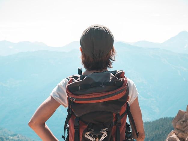 Um mochileiro da pessoa que olha a vista altamente acima nos cumes. paisagem expansiva, visão idílica ao pôr do sol. vista traseira, imagem enfraquecida.