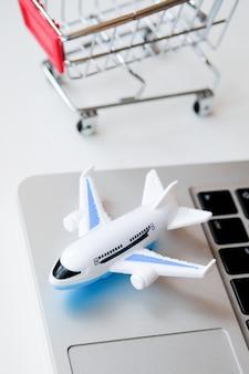 Um modelo de avião fica em um laptop ao lado de um carrinho. a compra de bilhetes para um voo através da internet.